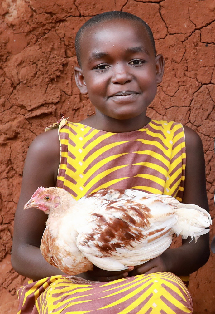 Glory holds one of the chickens her family has received thanks to Trócaire's local partner, Ishiara parish. The family have received 5 chickens, as well as training on disease control and poultry management. She has also joined a poultry group, where she