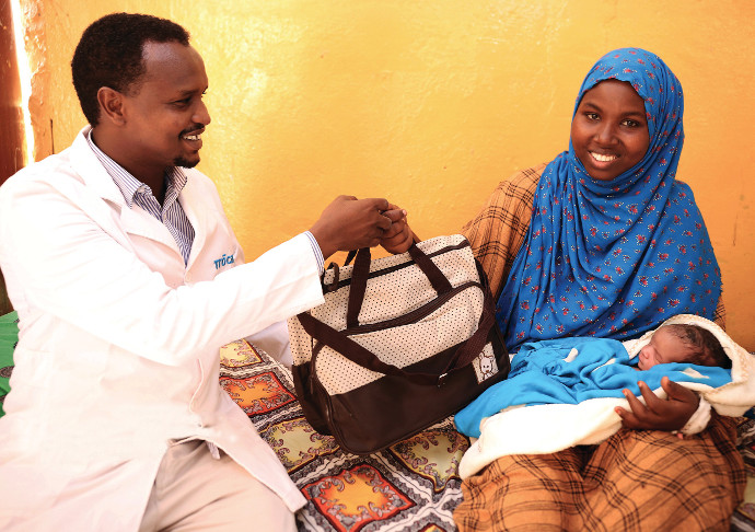 Nasra Mohamed holding her newborn baby is receiving a baby kit gift from Dr. Abdi as part of Trócaire's Somalia programme. The country has been badly affected by conflict and drought. Photo: Eyeris Communications/Trócaire.