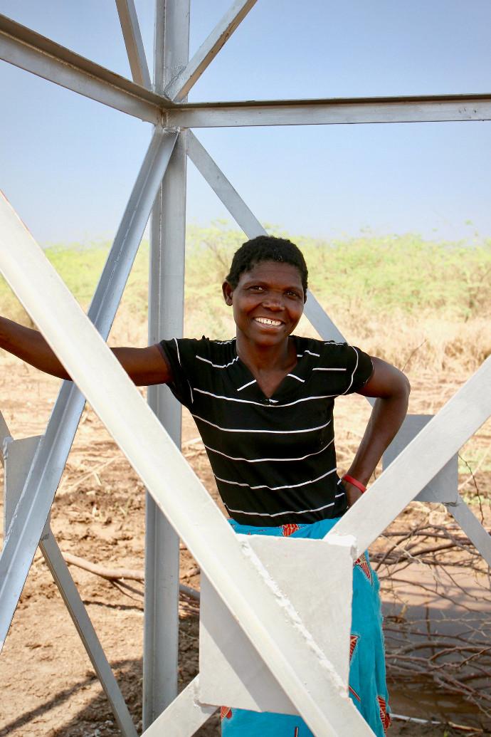 Stella Muithe stands under the village's new water pump. Photo: Alan Whelan/Trócaire.