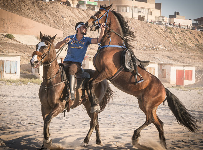 Abed Alla El Gefary on horseback along the beach in Gaza. El Gefary performs acrobatics on horseback to entertain the crowds along Gaza's beach. (Photo: John McColgan)