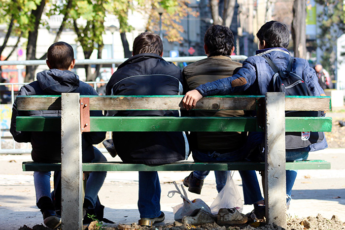 Young Afghan refugees sit on a park bench in Belgrade, Serbia