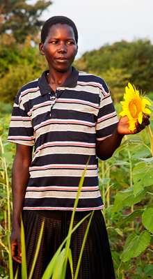 esther with sunflower in uganda