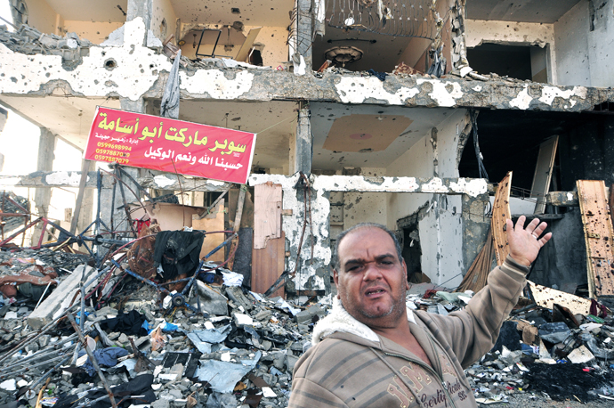 Ramadan Nurfil stands in front of a partially destroyed apartment block in Beit Hanoun