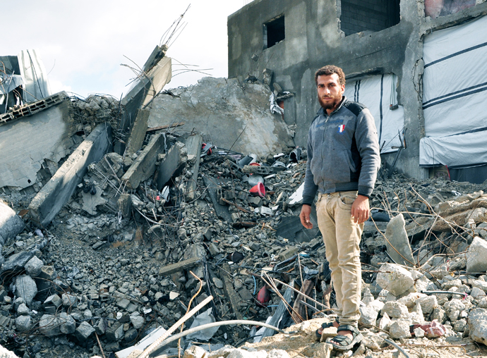 Mohammed Wahdan stands on the site of his destroyed home