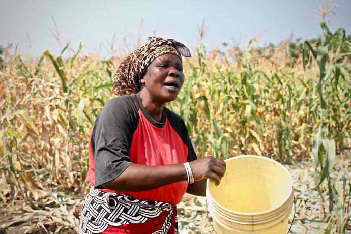 Lene Nanthabwe shows how she had to water her crops with a bucket before they received their water pumps for irrigating. Photo: Alan Whelan/Trócaire.