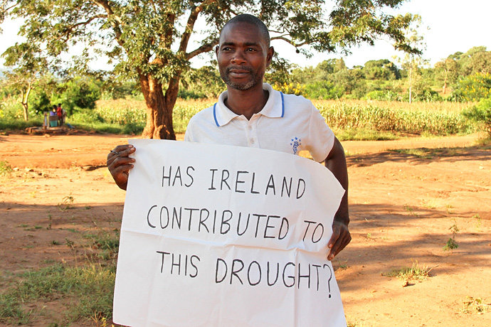 A man in Lilongwe, Malawi holding up a sign for Trócaire's Climate Change campaign. Malawi faces persistent drought due to Climate Change. Photo : Alan Whelan.