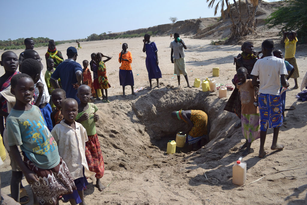 People dig for water in a dried up river bed in Kenya