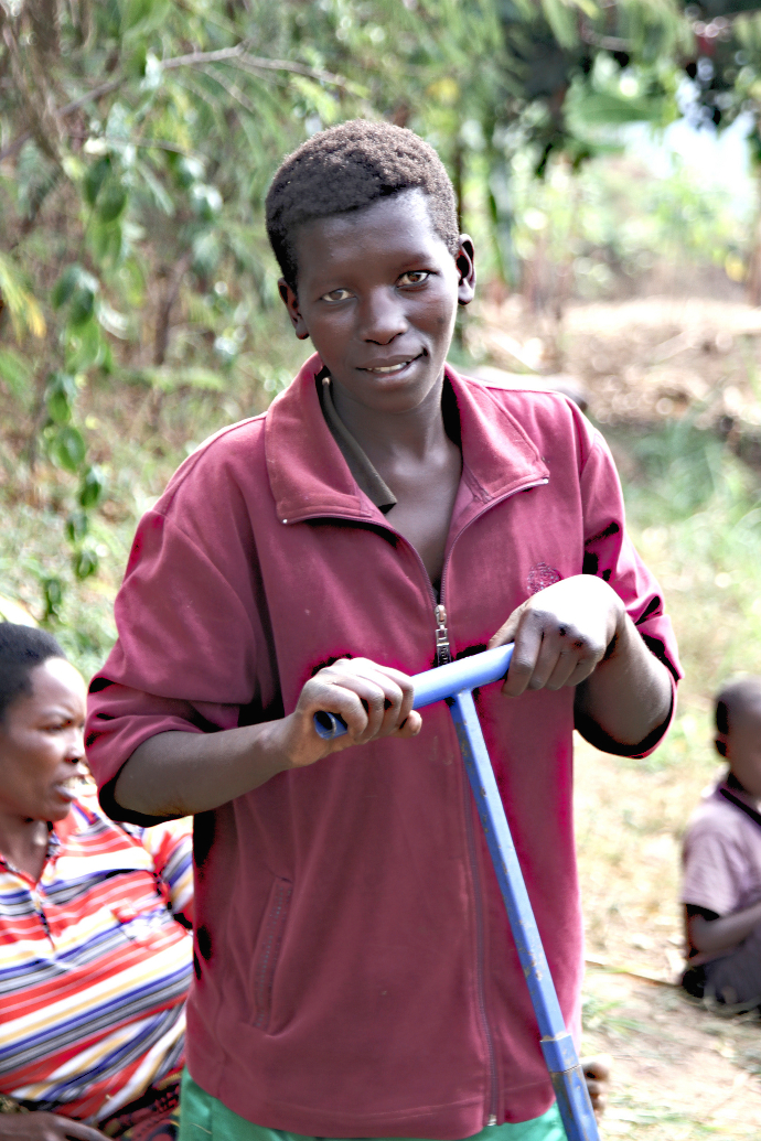 Francine Mujuyimana uses the treadle pump that moves water from the pond to the communal garden.