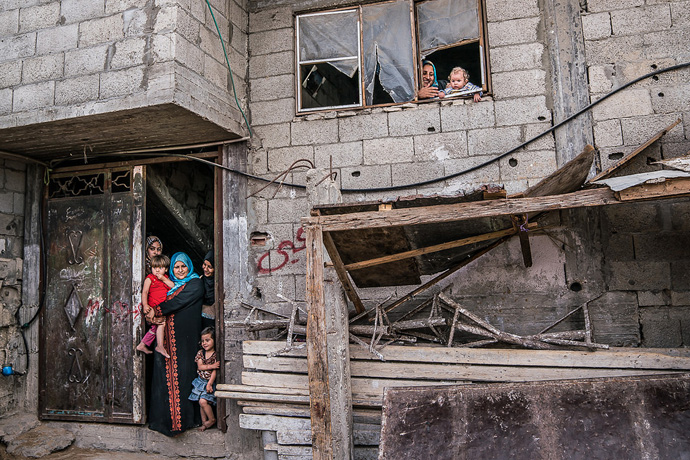 A family gathers outside their house in Gaza. (Photo: John McColgan)