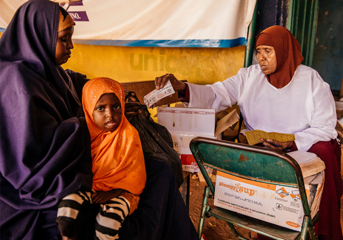 Idle Abdi Mohammed is given her weekly supply of Plumpy Sup for her daughter Zaynab by the nutritionist at Bula Hawa health centre