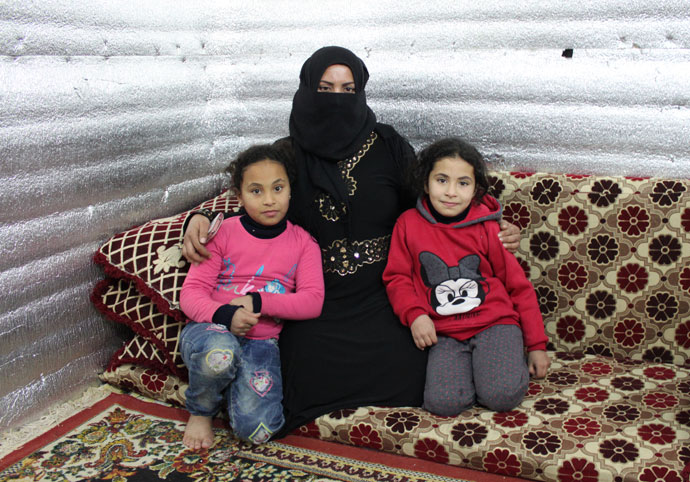 Nofa Dergham (33) with two of her daughters Dalaa (8) and Sydra (7). The family are living in a tent in a camp in the Beqaa Valley near the Syrian border.