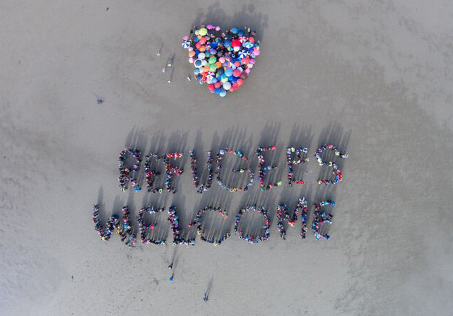 Spelling out Refugees Welcome on Sandymount Strand