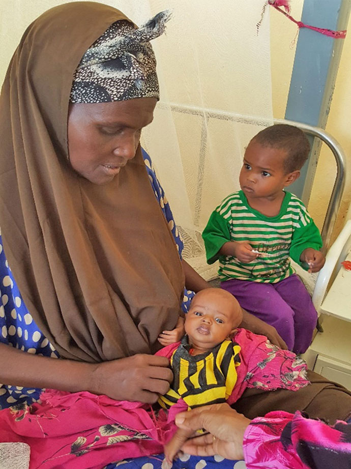 Shamso Abdi Hussein holding her grandson on the hospital bed