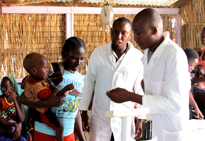 Healthcare workers advise mother at St Mary's Healthcare Clinic in Kalokol