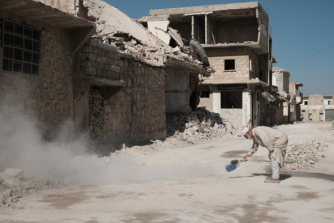 A man in Aleppo begins to clear dust amid the rubble, March 2017. Fears are that Idlib could face an attack on a similar scale to what happened in Aleppo. Photo : Patrick Nicholson / Caritas