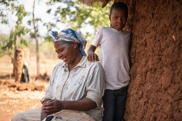 Teresina (45) with her youngest son Amos outside their home in Tharaka Nithi