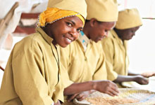 Vestine Uwizeyinana and Claudine Tuyishimire sorting grain at Muhanga Food Processing Industries.