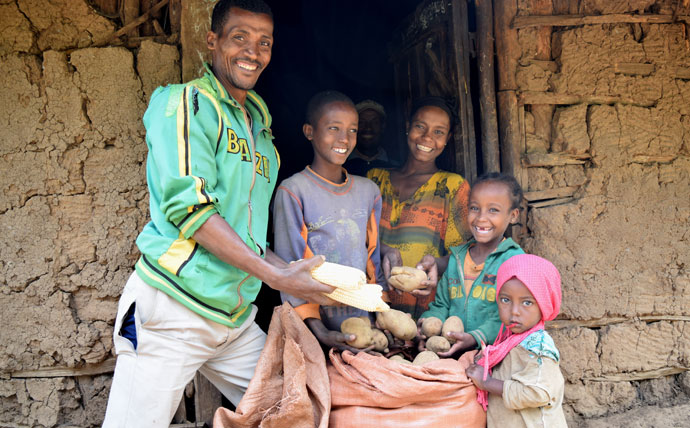 Abraham Abamo and his family proudly display their crop