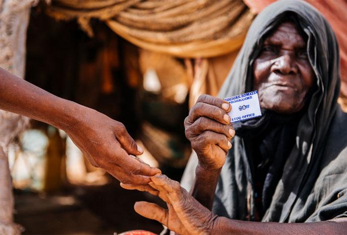 Dahabu Ali, an elderly member of Dhuyuleh camp for internally displaced people in Somalia, receives a Trócaire ration card, May 2017. Photo: Amunga Eshuchi