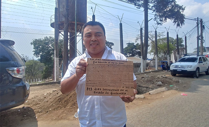 Abelino Chub Caal holds up a sign highlighting the 813 days he spent wrongfully imprisoned for his work defending the land rights of indigenous communities in Guatemala following his release photo @LibertadAbelino