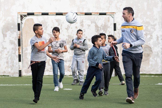 Armagh's All-Ireland winner and professional counsellor Oisín McConville gives a Gaelic football skills training session to young Palestinian refugees in the Aida refugee camp in Bethlehem. Photo: Garry Walsh/Trócaire.