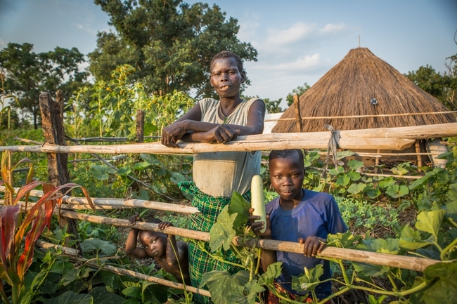 Lakot Linda in her thriving permagarden outside of her hut with two of her grandchildren. Photo : Sarah Fretwell.