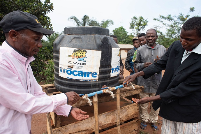 Thousands have been provided with hand-washing stations in the DR Congo to prevent Ebola. Here Twal Umande (48) and Bahati Imulali (20) wash their hands. Photo : Garry Walsh / Trócaire