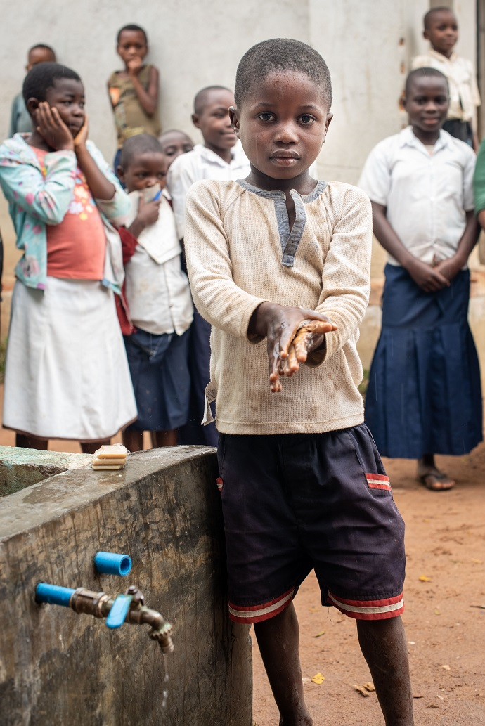 Six year old Kampale washes his hands at a water tank provided by Trócaire to his school, to improve hygiene to halt the spread of ebola. Photo : Garry Walsh / Trócaire