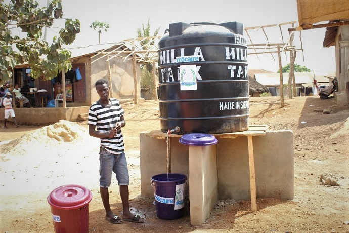 Supporting good hygiene practices. Mohamed Lamin Sumah uses a water tank for handwashing at the temporary screening booth at the border between Sierra Leone and Guinea. Photo : Alhassan Sesay / KADDRO
