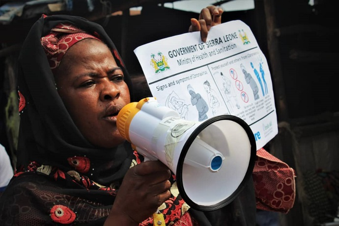 Kaddy Mansaray, Chair of the Funkia Market Women's Association provides COVID prevention information at the market with a poster and megaphone. Trócaire's local partner SEND Sierra Leone is engaging communities on COVID prevention measures.  Photo : Jonathan Bundu / SEND - SL