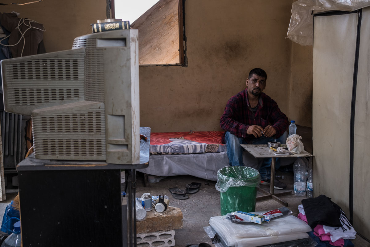Adnan Asaf, 42, sits in his home affected by the explosion.