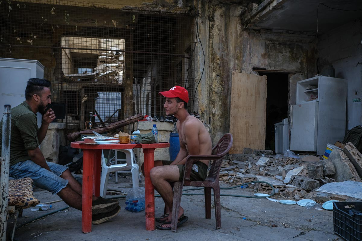 Syrian refugees sit in what is left of their houses, a kilometre away from Beirut's port where the explosion occurred. Lebanon hosts over a million Syrian refugees and many of those refugees already struggle with poverty and discrimination.