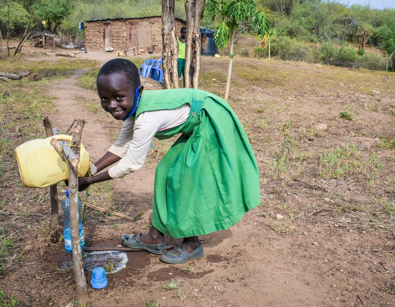 7 year old Joy-Faith washes her hands to prevent the spread of Covid. The home-made tap was made out of recycled household items. Photo : Denis Kioko / Trócaire