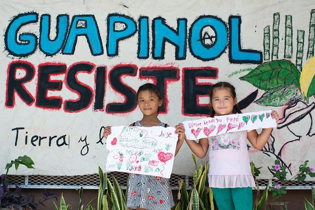 """Two daughters of the imprisoned human rights defenders from Guapinol in Honduras, Liss Jireth Cedillo Zúniga (7) and her friend Cristhel Alejandra Romero Portillo, holding their drawings in front of the Public Ministry in Tegucigalpa, Honduras. The sign in the background says """"Guapinol is resisting"""". Photo: Giulia Vuillermoz"""