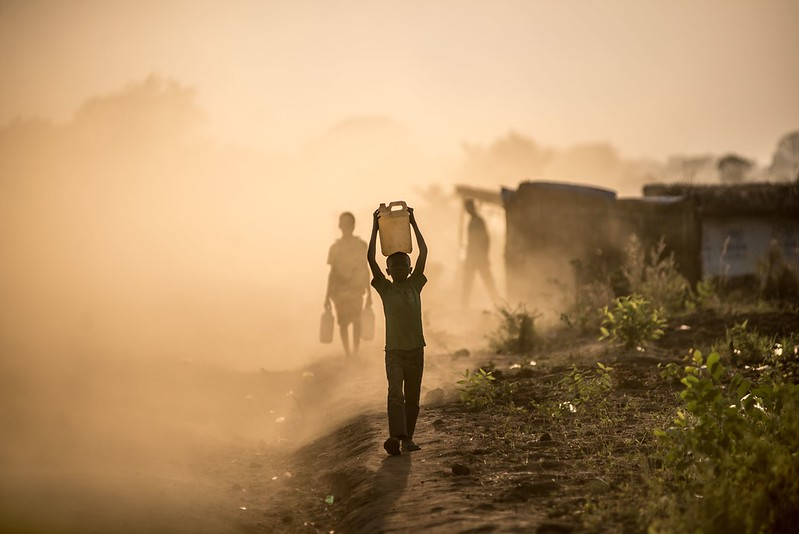 South Sudanese refugee children carry water through Bidi Bidi camp in Uganda. Photo : Tommy Trenchard