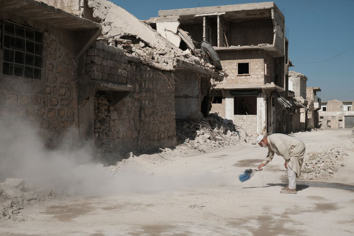 A man works to sweep the rubble in the devastated Syrian city of Aleppo. Photo by Patrick Nicholson/Caritas