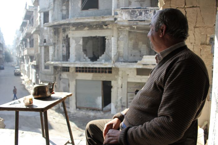 60 year old Abd Al Maseeh looks out at the destruction in the Syrian city of Homs. Photo: Caritas Internationalis
