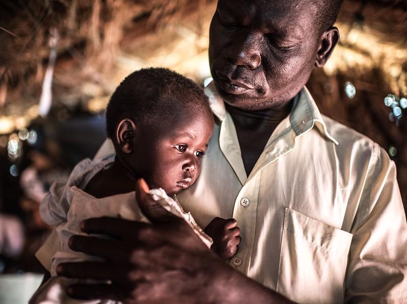 Joseph Malis, 39, holds his daughter in Bidi Bidi refugee camp, Uganda. Photo : Tommy Trenchard
