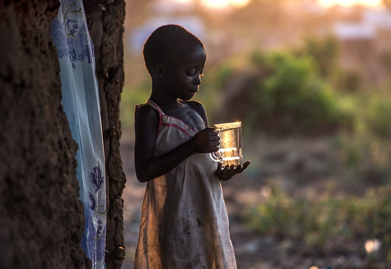 South Sudanese refugee Tabu Ruth brings water to her father, outside the family's new home in Bidi Bidi camp. Photo : Tommy Trenchard