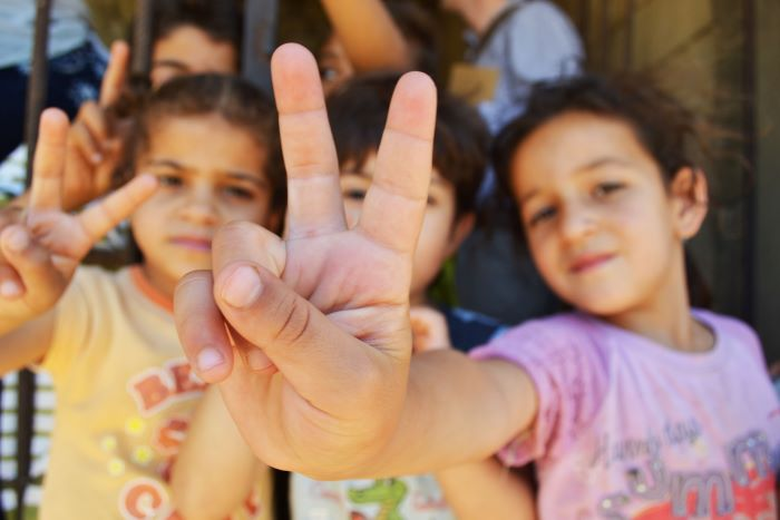 Syrian refugee children at a half-built apartment block near Reyfoun in Lebanon, close to the border with Syria, give the peace sign. Photo: Eoghan Rice