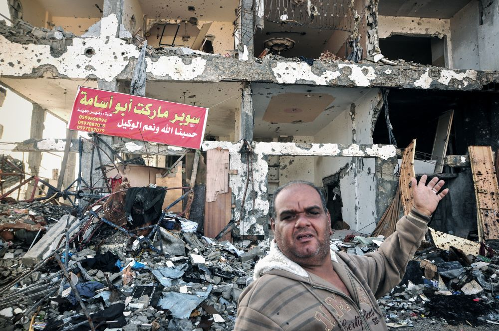 Ramadan Nurfil stands in front of a partially destroyed apartment block in Beit Hanoun in 2014. His shop was destroyed and he had no option but to keep living in his apartment in the building. Photo: Garry Walsh
