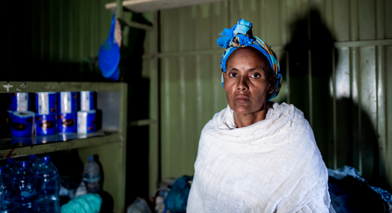 Lem Lem Mebrahtu, 40, sits inside her family shop. Since the conflict in Tigray started she has not had regular access to electricity or water and lives in constant fear that her shop will be looted.